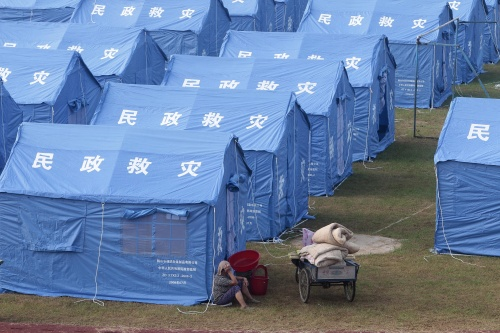 In Pictures A Villager Rests Outside A Tent At A