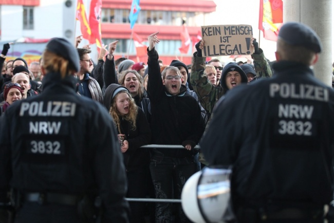 German police stand in front of demonstrators protesting against a rally by the anti-Islam PEGIDA movement of North Rhine-Westphalia and right-wing party Pro Koeln, outside the main station in Cologne, Germany, January 09, 2016.